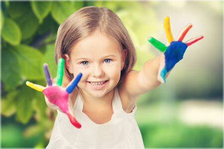 Girl with hands painted in colorful paints ready to make hand prints Stock Photo