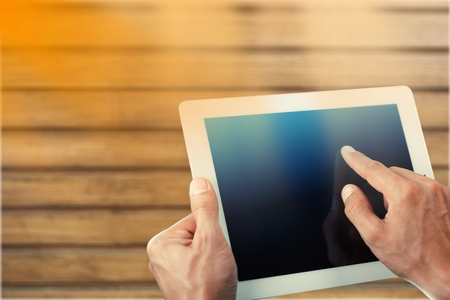 Top view shot of a woman holding digital tablet with a blank screen- closeup, fem a hands holding blank digital tablet against beautiful wooden copy space area, flare sun light, filtered image Stock Photo