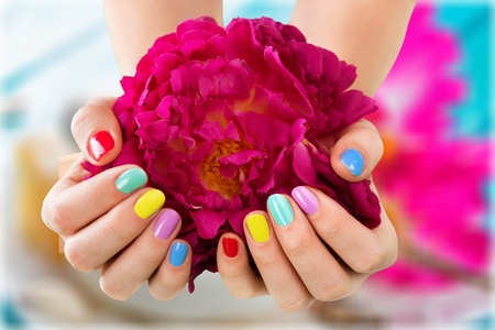 Close-up Of Womans Hands With Nail Varnish On Flower