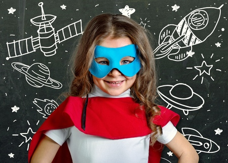 Happy little asian girl kid in astronaut suit doodle chalk board drawing & universe space out of earth planet on school green chalkboard background: World UFO day creative educational conceptual idea Stok Fotoğraf