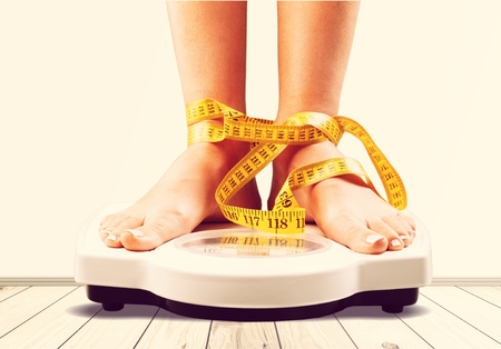 Woman on scales and measuring tape