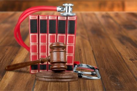 Mazo y estetoscopio del concepto de la ley de la medicina en los libros aislados en el fondo blanco