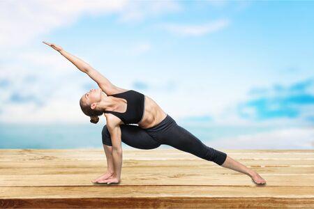 young beautiful yoga posing Utthita Parsvakonasana on a gray studio background