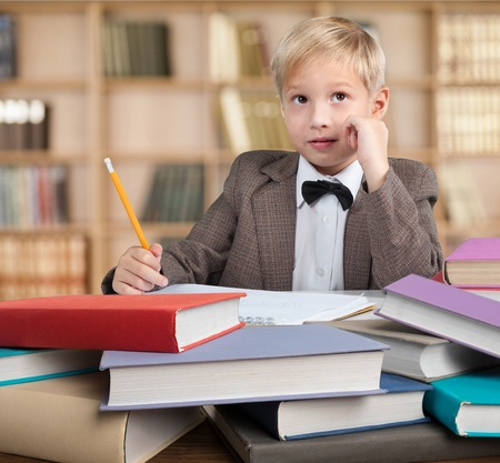 Child against the rain of numbers and letters with a book over his head Stock Photo