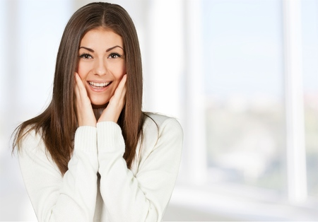 Close-up of a young woman looking excited against white background