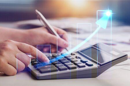 Fermez la jeune femme avec la calculatrice en comptant faire des notes à la maison, la main est écrite dans un cahier. Épargne, finances, concept.