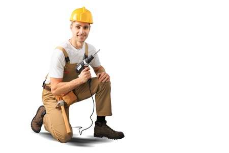 Serious Male Construction Worker with short black hair in uniform using drill - Isolated Standard-Bild