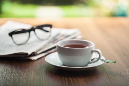 Newspaper reading glasses coffee cup and mobile phone on business desk business newspaper background concept.
