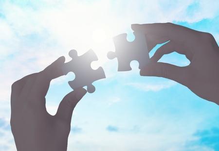 Hände setzen Puzzleteile