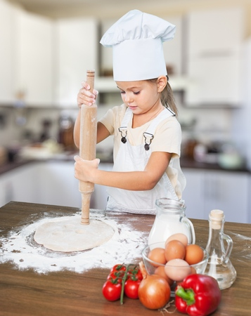 Happy little chef smeary with flour stretching the dough