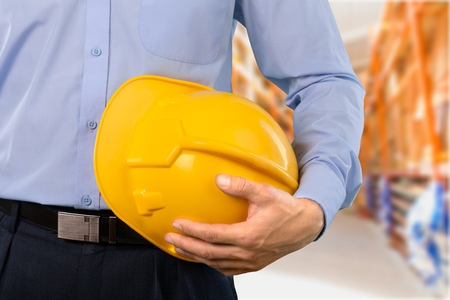 Close-up shot of a foreman holding a hardhat on the construction site Stock Photo