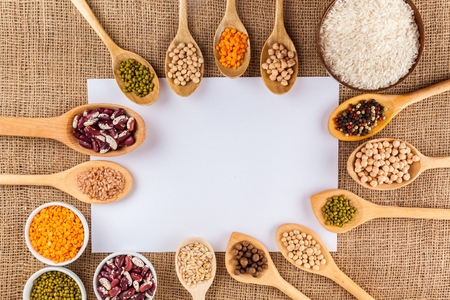 various grain, beans, legumes, peas, lentils in spoon on the sackcloth background