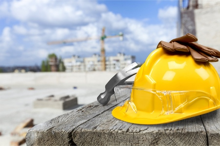 Yellow hard hat and gloves on wooden table