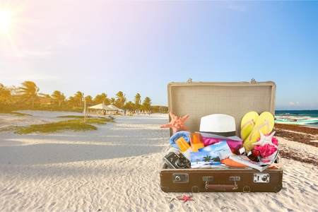Beach accessories In open suitcase on beach