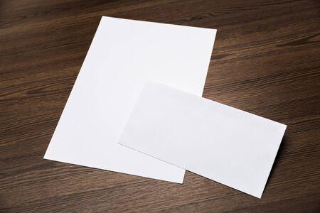 Blank corporate identity package business card envelope & letter on wood floor.