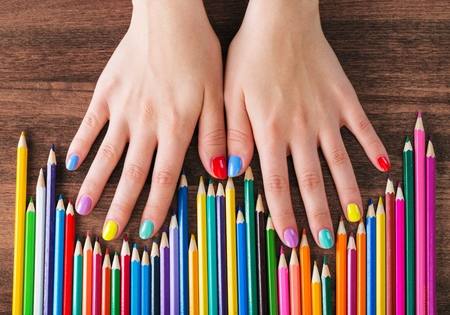 Color rainbow pencils and teenagers hands with multicoloured nails Standard-Bild
