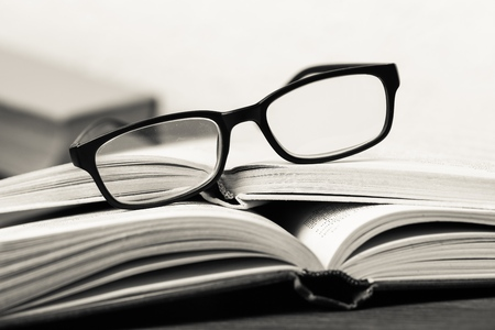 a pile of books and glasses symbolizing the concept of reading habit or studying Standard-Bild
