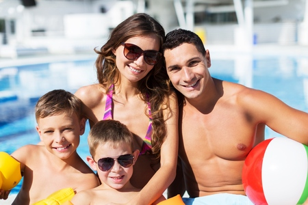Happy big family having fun at the pool, spending summer vacation together, wearing funny colorful sunglasses, enjoyment and pleasure concept Standard-Bild