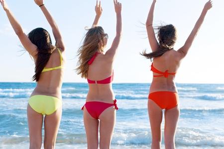 Sexy backs of five beautiful women in bikini on the beach Standard-Bild