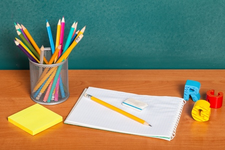 Teachers desk with a color pencil, notebook and other equipment.
