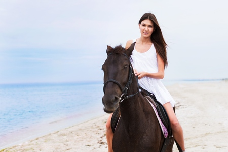 beautiful girl with long blond hair riding on a brown horse on the shore of Indian Ocean on the island of Mauritius Banque d'images