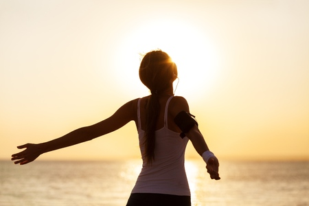 healthy lifestyle fit woman open arms under the sunrise at sea