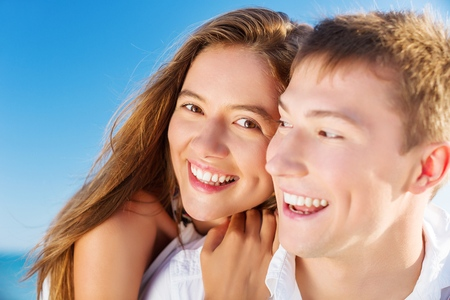Happy romantic couple on beach in love. Portrait of joyful young multi-ethnic young couple embracing each other having fun outdoors during summer holidays vacation travel. Asian woman, Caucasian man.