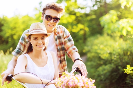Handsome man taking his girlfriend on bicycle rack