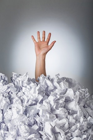 Hand reaches out from big heap of crumpled papers 版權商用圖片