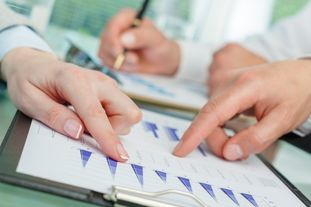 Unrecognizable business person analyzing graphs and taking notes Standard-Bild