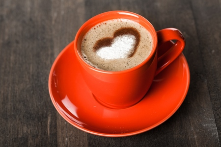 Red cup with cappuccino and heart decoration over foam. Valentines day cup. Love concept