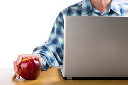 Man Working with Laptop while Holding an Apple