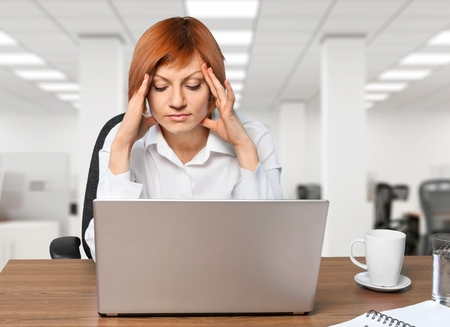 Portrait of young bored attractive woman at office desk, feeling hopeless, lost motivation and inspiration, sitting with arms crossed behind the head and looking at laptop screen with tired expression