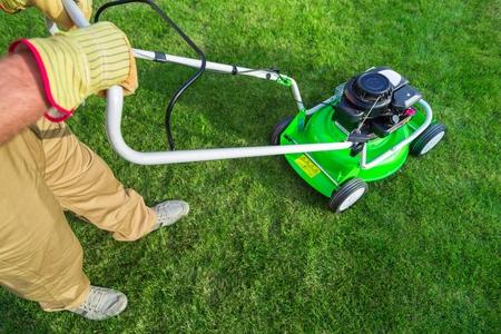 Closeup of a Gardener Using a Lawn Mower Stock Photo