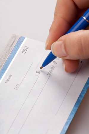 Womans Hand Writing a Check on Grey Background Stock Photo