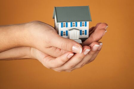 Womens Cupped Hands Holding a Model of a House on Orange Background