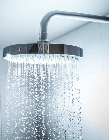 Shower Head with Water Stream on Grey Background Archivio Fotografico