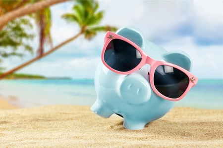 Summer piggy bank with sunglasses on the beach 写真素材