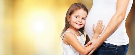 彼女の娘が腹の中で赤ちゃんを聞いている妊娠中の女性