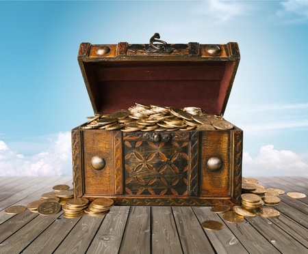 Open treasure chest filled with gold coins isolated on white