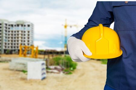 Engineer holding hard hat Stock Photo