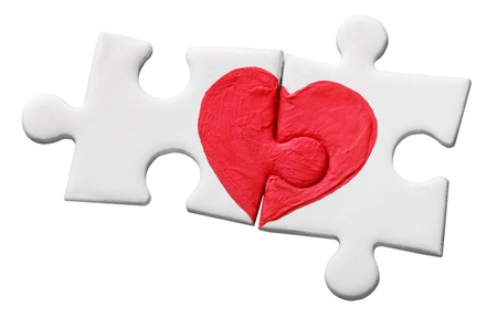 closeup of two pieces of a puzzle forming a heart on a rustic wooden surface, depicting the idea of that love is a thing of two Stock Photo