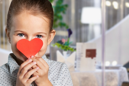Little girl and red heart