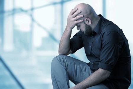 Hombre triste sentado en la habitación. Foto de archivo