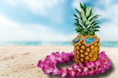 Ripe attractive pineapple in stylish sunglasses heart shape and gold headphones on sand against turquoise  sea water. Tropical summer vacation concept. Summer sunny day on the beach of tropical island