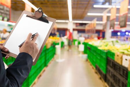 Businessman using the tablet and writing the order stock on Supermarket blur background, business technology concept Stock Photo