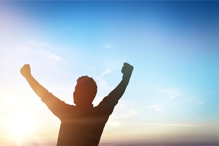 Silhouette man happy with hands rise up on beautiful sky Stock Photo
