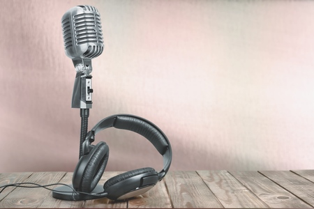 Retro microphone with headphones on table. Vintage old style sepia photo 스톡 콘텐츠