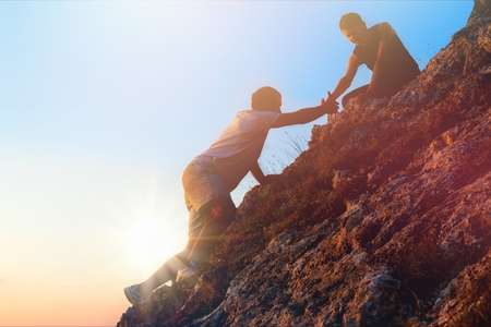 People helping each other hike up