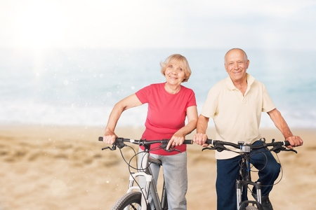 Full length of senior couple with their bicycles at the beach Stock Photo